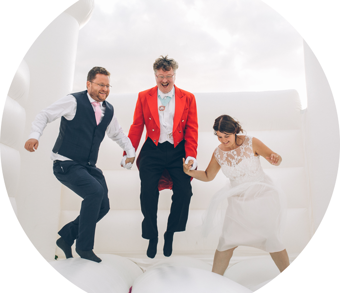 Toastmaster with bride and groom on a bouncy castle